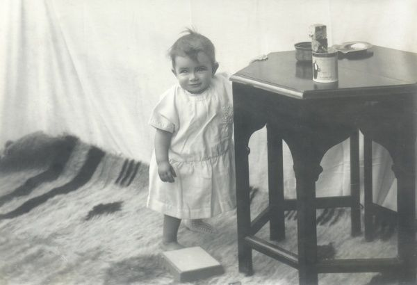 A smiling toddler leaning against a hexagonal table with various items on it -- a tin, a bowl, two building bricks and an ashtray. A furry rug is on the floor
