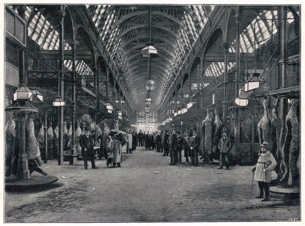 The vast interior of Smithfield meat market, with carcasses hanging from hooks all down the central aisle