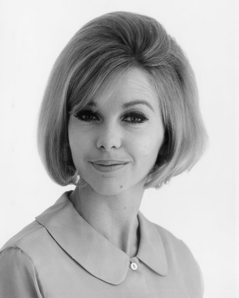 Head and shoulders portrait of a woman in a plain blouse. Date: late 1960s
