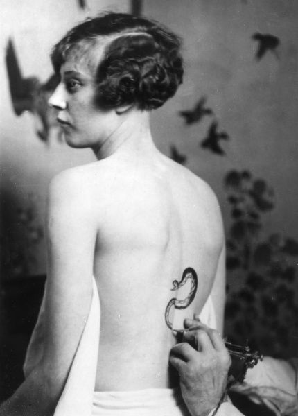 The latest craze for feminine beauty is the tattooing of the back with serpents, butterflies, etc. This picture was taken in a London salon. Date: 1929