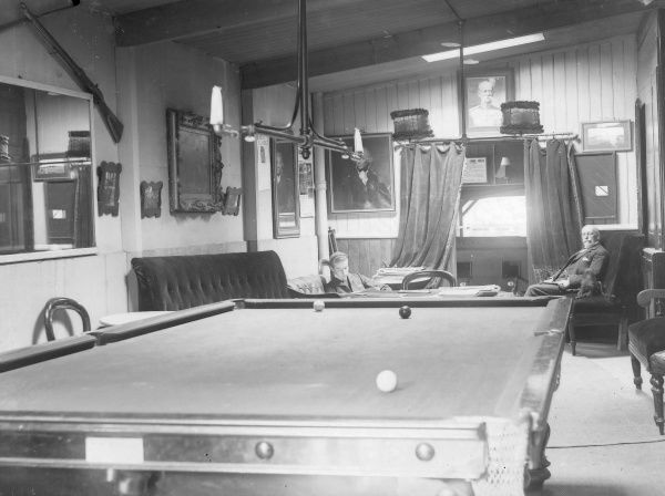 View inside a snooker room, with two players. The snooker table is in the foreground, with three balls on it. The players are both seated in the background