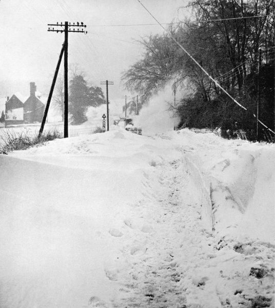 A snow plough bulldozes its way through deep snow on Westerham Hill in Kent on a road that had been impassable for days during the very cold conditions of the winter of 1963