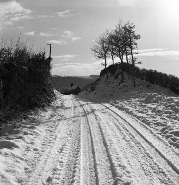 A snow-covered country lane, tracks in the snow giving evidence to the passing of several motor vehicles. Photograph by Norman Synge Waller Budd
