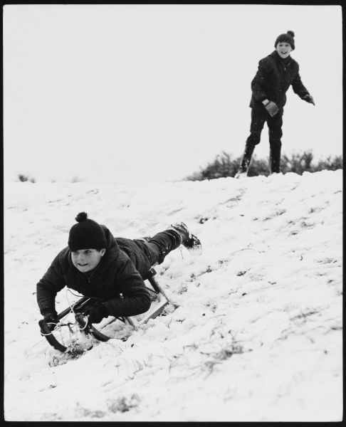 Two boys having fun and games with their sledge in the snow!