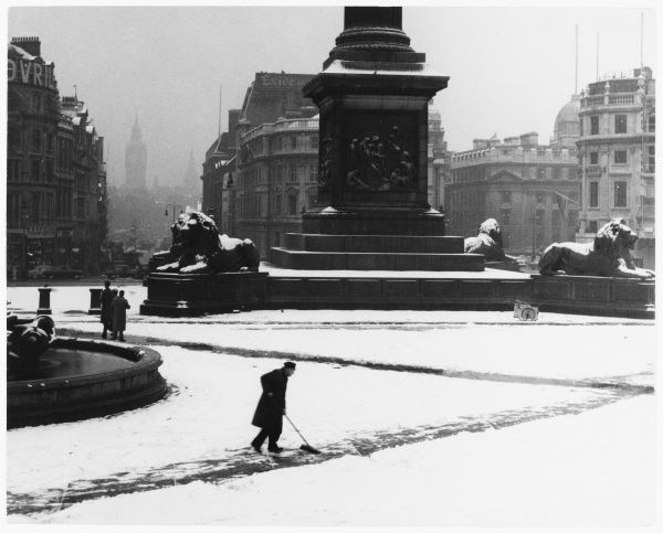 A man sweeps a path in the heavy snow at the base of Nelson's Column in Trafalgar Square. Note Landseer's lions covered in snow