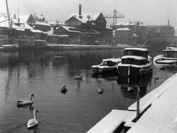A winter study at King's Staith, York, Yorkshire, England, with it's snow-covered quays and pleasure boats moored on the canal side. Date: 1950s