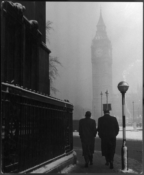 Two shady-looking figures with their hands in their pockets, just about to turn a corner in Westminster in snowy weather