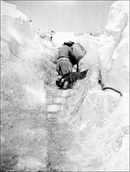 A man making his way up some steps cut into the snow on a mountain in Kashgar, western China. Photograph by Ralph Ponsonby Watts