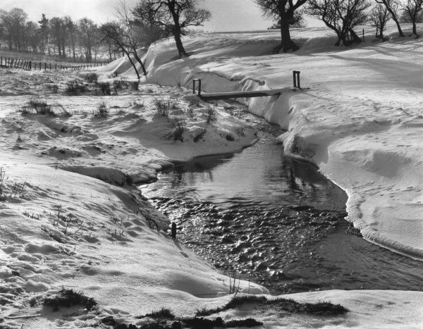 A fine winter setting by the snow-covered banks of the Lead Burn, Howgate, Midlothian, Scotland. Date: 1960s