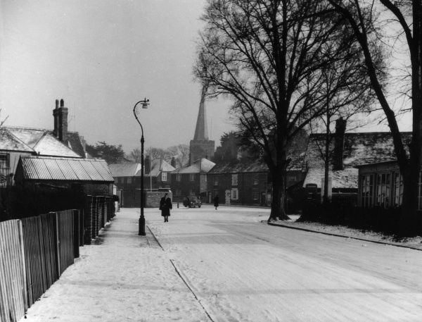 Winter in Sussex, England - snow-covered Glebe Road, in Tarring, with St. Andrew's church in the background. Date: 1950s