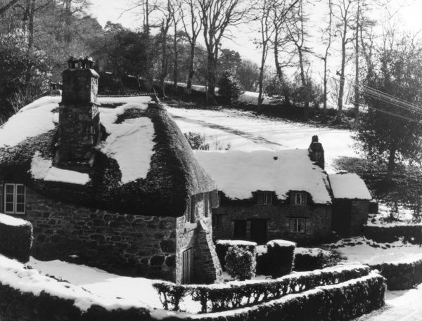 Winter snow on the lovely thatched cottages at Buckland- in-the-Moor, Dartmoor, Devon, England. Date: 1950s