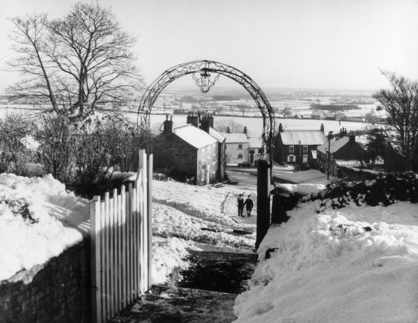 Winter snow scene, taken from the churchyard of Crayke village, Yorkshire, England. Date: 1950s