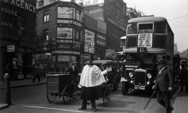 Scene in a busy London street: a policeman wearing a white cape directs the traffic