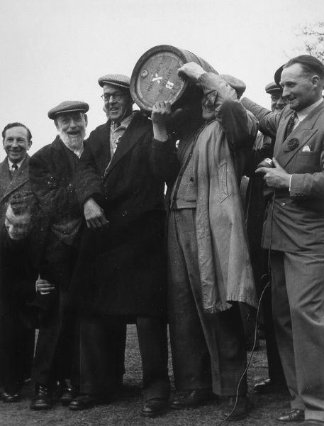 A group of men at a championship game of marbles at Tinsley Green, Sussex (held every Good Friday): the winner receives a cask of beer Date: 1950s