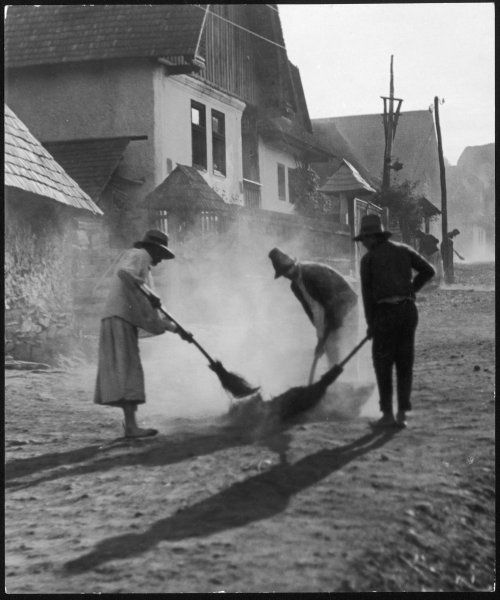 Folk sweep up the dust on the streets of a Transylvanian village