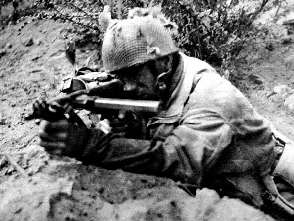 Photograph showing a soldier of the British First Airborne Division firing his Sten gun at Germans near Arnhem, Holland, September 1944