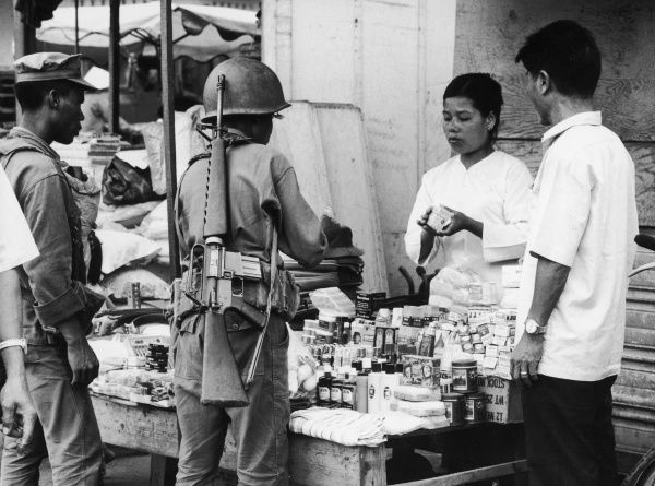 Phan Rang: a Vietnamese soldier, with an extremely large rifle slung over his back, buys goods from a stall holder