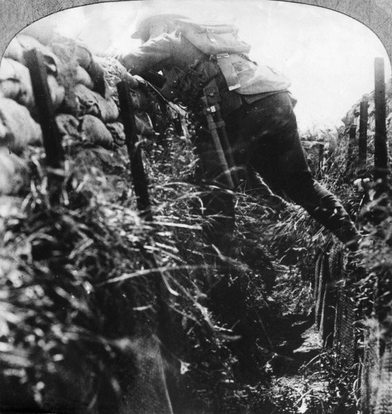A soldier emerging from a trench to rush a German position during the First World War. Date: 1914-1918
