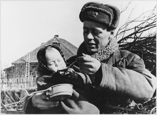Red Army soldier feeds an orphaned child