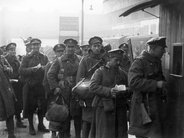 Soldiers on 14 days' leave changing their French money into English currency at the change box on a railway station platform during the First World War. Date: 1914-1918