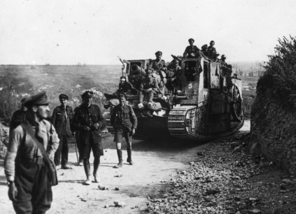 A group of soldiers marching along a road with a field gun on a tank during the First World War