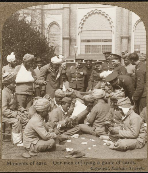 Sikh and English soldiers in the British army enjoy a relaxed time chatting and playing a game of cards