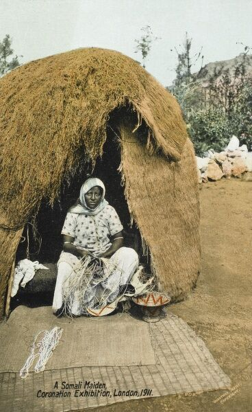 A Somali Woman weaving in the entrance to her reed hut - an 'exhibit' at the Coronation Exhibition of 1911 in London