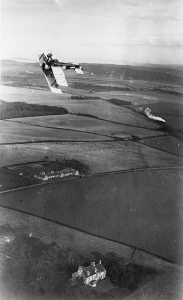 A British Sopwith Camel fighter biplane looping the loop above the countryside during the First World War. Photo taken from another aircraft. Fields and houses can be seen below, and a passing steam train. Date: 1914-1918