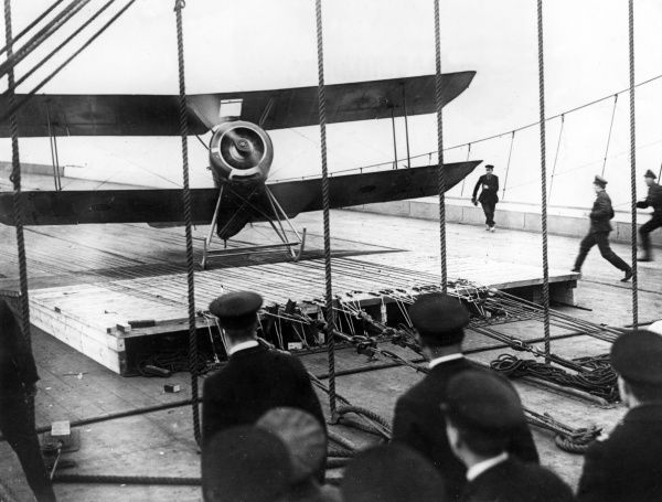 A Sopwith Pup biplane landing on the deck of the aircraft carrier HMS Furious (a modified Courageous-class cruiser) during the First World War. Launched in 1916, HMS Furious served in both World Wars and was scrapped in 1948. Date: 1916-1918