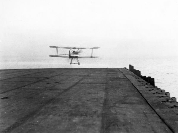 A Sopwith Pup biplane taking off from the deck of the aircraft carrier HMS Furious (a modified Courageous-class cruiser) during the First World War. Launched in 1916, HMS Furious served in both World Wars and was scrapped in 1948. Date: 1916-1918