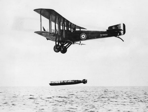 A British Sopwith T1 Cuckoo bomber biplane launching a practice torpedo over the sea towards the end of the First World War. It was powered by a Sunbeam Arab V8 200 horsepower engine. Date: circa 1918