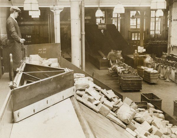 A postal worker at the General Post Office (GPO), at Mount Pleasant, north London, sorts out parcels on a conveyor belt in the warehouse