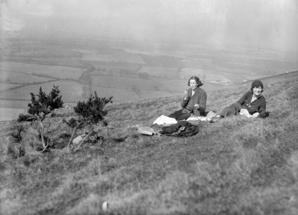 Two young women enjoy a bracing picnic on the South Downs, England. Date: early 1930s