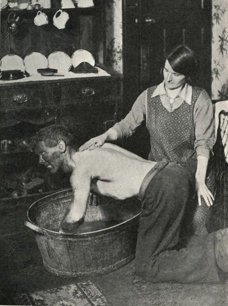 A South Wales miner, face and forearms black with coal-dust, washes at home in a large tin bath. His wife helps wash his back. Date: circa 1936