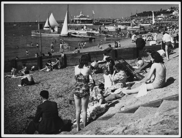 Holidaymakers on the beach at Southend-on-Sea, Essex, England. A sign offers boat trips for adults at 1s (shilling) each and children at 6d (sixpence) each