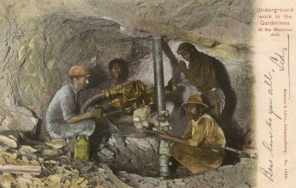 Working underground in a South African goldmine - using a machine drill Date: 1907