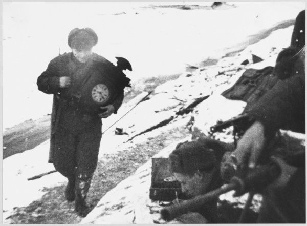 Russia : a Soviet soldier retrieves a clock from the rubble of a village devastated by the German attack