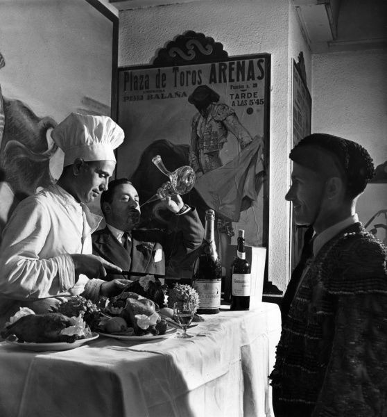 A Spanish matador waits in front of a buffet, while the chef dishes up and a man in a suit swigs wine from a porron! Date: 1960s