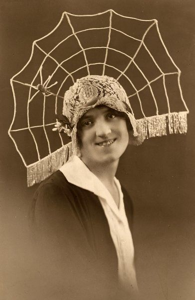 A rather unattractive young woman models a fantastical lace cloche hat with an elaborate spiders web radiating from the back - complete with spider