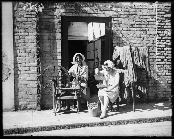 Two old dames using combs and and a traditional spinning wheel to spin wool which will be used on a hand loom, Sandwich, Kent, England