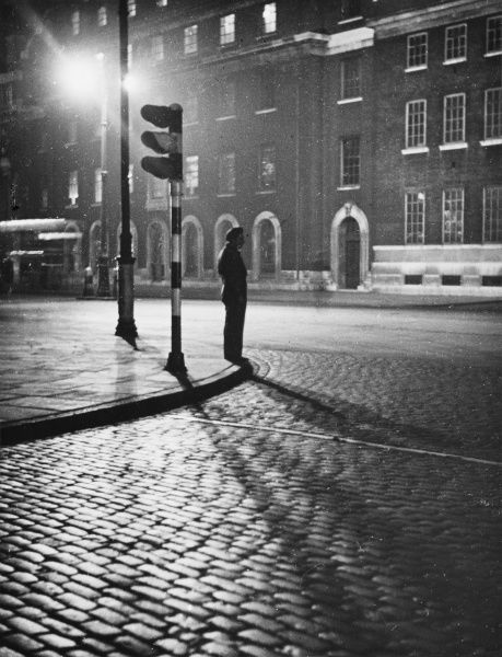 Midnight: A man in a beret waits next to some traffic lights on the Euston Road, London, in this atmospheric photograph