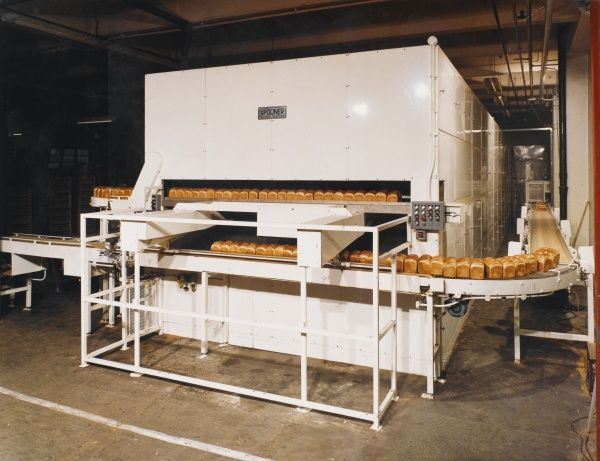 A immense Spooner Travelling Oven - with baked loaves of white bread transported from the large central baking oven round a periphery conveyor belt and roller system to the next stage of the process (packing). Photograph by Heinz Zinram