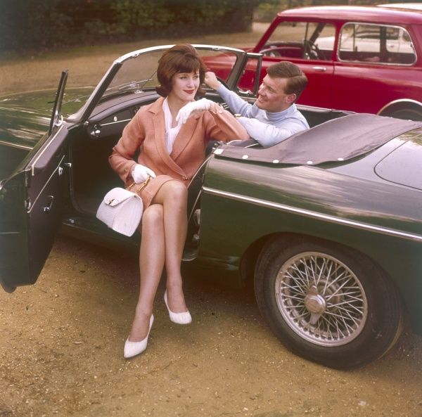 A couple posing in a classic racing green 'MGB' sports car. Introduced in 1962, the MGB was originally available only as a convertible and proved to be an immediate hit. Date: 1960s