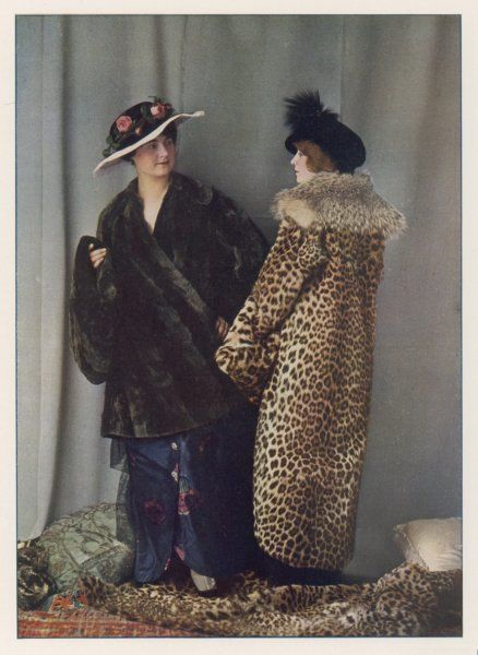 A short, wrap-over fur coat & flat muff in a dark coloured fur; full-length coat in an unspecified spotted cat fur with a contrasting collar. N.B fur & oriental rugs & cushions