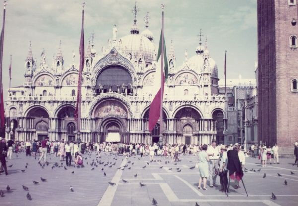 St Mark's Cathedral and Piazza in Venice, Italy, on a busy day, with pedestrians and pigeons. Date: 1968
