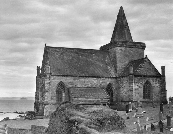 The fine church at St. Monance, a small fishing village on the Firth of Forth, Fifeshire, Scotland. Bass Rock can just about be seen in the distance. Date: 14th century