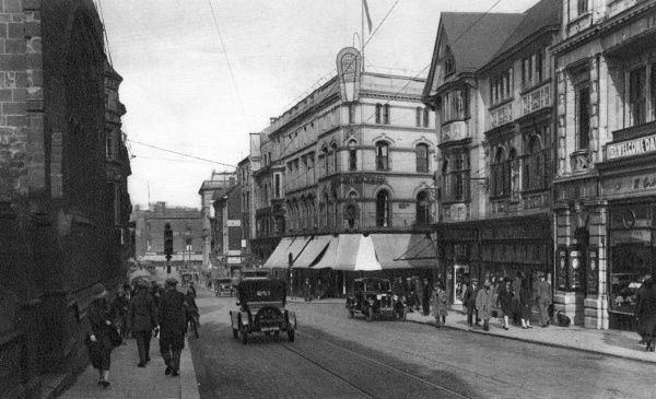 View of St Peter's Street, a busy shopping street in the centre of Derby, with traffic and pedestrians. St Peter's Church is the building on the left. Date: circa 1920