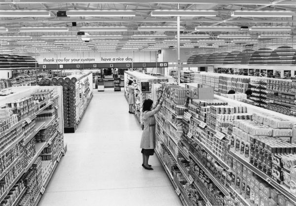Two female employees stack the shelves of an almost empty supermarket