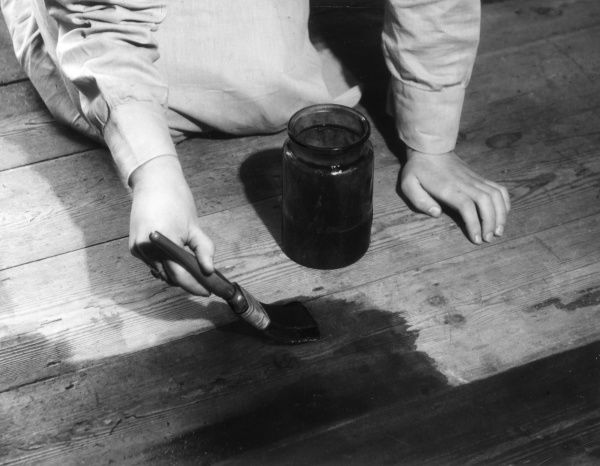 Using a brush to stain floorboards with permanganate of potash (potassium permanganate). Date: 1930s