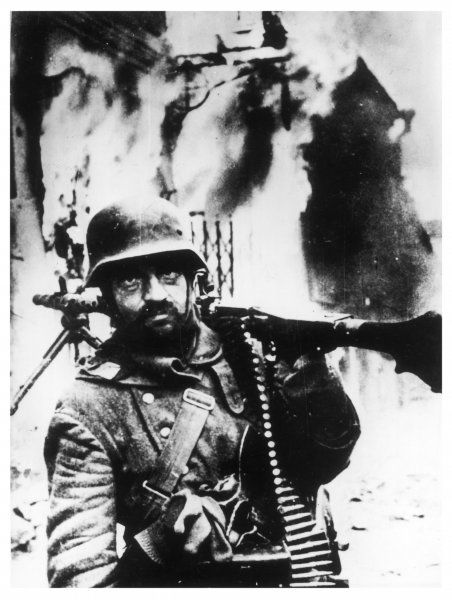 Despite impending defeat, an exhausted German soldier fights on until the bitter end. War- torn Stalingrad burns behind him